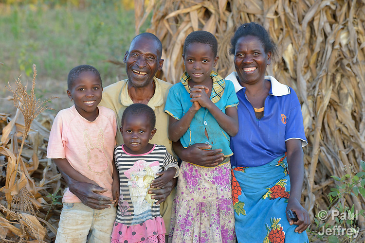 Joseph Nkhoma and his wife Jane Salanda take a break from shucking corn to pose with their children Beauty, 8, Sibosiso, 5, and Mphatso, 3, on their farm in Edundu, Malawi. They and other farmers in the village have benefited from intercropping and crop rotation practices they learned from the Malawi Farmer-to-Farmer Agro-Ecology project of the Ekwendeni Mission Hospital AIDS Program, a program of the Livingstonia Synod of the Church of Central Africa Presbyterian.