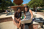 Neema Loy, left, a Ph.D. student in linguistics from Tanzania, and Marcella Cascione Netto, a masters student in linguistics  from Brazil, confer with each other at the fountain in the quad.  Photo by Kevin Bain/Ole Miss Communications