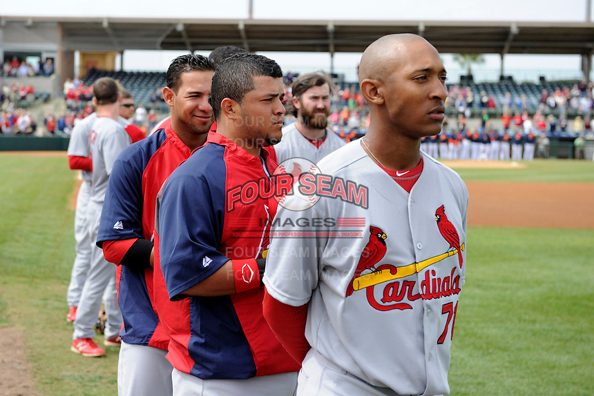 St. Louis Cardinals pitcher Sam Freeman #71, catcher Jesus Montero and members of the bullpen during the national anthem before a Spring Training game against the Houston Astros at Osceola County Stadium on March 1, 2013 in Kissimmee, Florida.  The game ended in a tie at 8-8.  (Mike Janes/Four Seam Images)