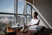 "China - Ningxia - Yinchuan - Has Linhai, 65, looks out the window of his office overlooking the Chenjia Lake, in Yinchuan. A former government man, Hao is the chairman of the wineries' federation of Ningxia and one of the driving forces behind the region's recent success. ""Wine is a cultural product"", he explains. ""We should use it as a window to connect Ningxia and China with the rest of the world rather than fo-cusing on its economic value""."