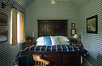 The walls and ceiling of this small bedroom are covered in blue and white checked wallpaper