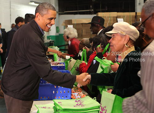 United States President Barack Obama shakes hands with an unidentified woman as he fills bags with produce at the Capital Area Food Bank in North East Washington DC on Wednesday, November 23, 2011.  .Credit: Dennis Brack / Pool via CNP