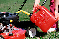 POURING GASOLINE<br /> Gasoline Being Poured Into A Lawnmower
