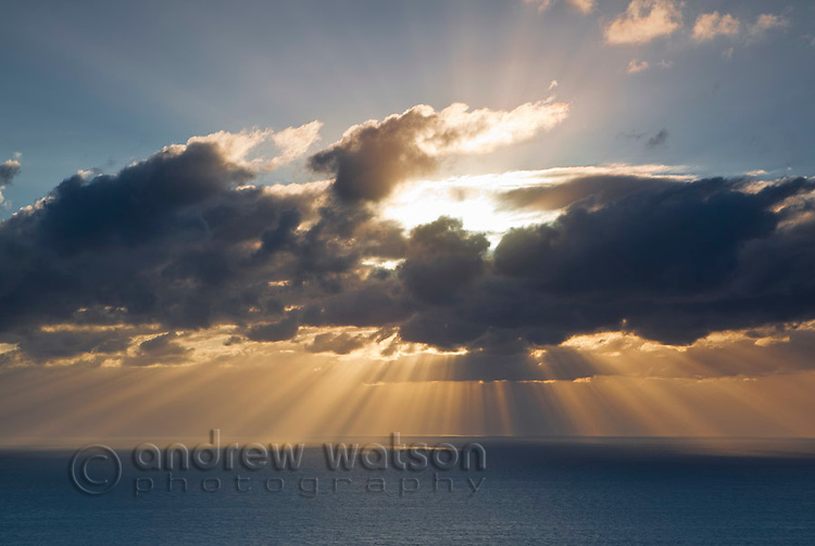 Sun bursting through clouds above Coral Sea.  Cooktown, Queensland, Australia
