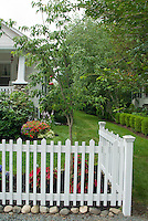 White picket fence, caladium annual plants with hosta perennials, front house, lawn grass, pretty curb appeal landscaping, hummingbird feeder, dogwood Cornus, blue hydrangea, rhododendron, hanging basket of Calibrachoa flowers, neat rows of boxwood as foundation plantings