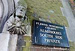Statue and sign at entrance to St John's Winchester Charity Almshouses, Winchester, Hampshire, England