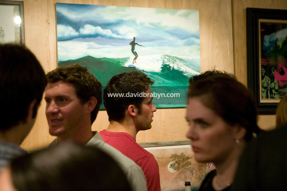 Visitors look at artwork at a surf-related exhibit in New York City, United States, 5 May 2005. Photo Credit: David Brabyn.