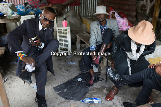 "KINSHASA, DEMOCRATIC REPUBLIC OF CONGO - FEBRUARY 10: Sapeurs shine their shoes in a restaurant  with his designer label clothes while paying his respects to Stervos Nyarcos, the founder of the kitendi religion, which means clothing in local language Lingala. Nyarcos was known as the leader of the Sape movement, at Gombe cemetery on February 10, 2017 in Kinshasa, DRC. The word Sapeur comes from SAPE, a French acronym for Société des Ambianceurs et Persons Élégants. or Society of Revellers and Elegant People. and it also means, .to dress with elegance and style"". Most of the young Sapeurs are unemployed, poor and live in harsh conditions in Kinshasa, a city of about 10 million people. For many of them being a Sapeur means they can escape their daily struggles and dress like fashionable Europeans. Many hustle to build up their expensive collections. Most Sapeurs could never afford to visit Paris, and usually relatives send or bring clothes back to Kinshasa. (Photo by Per-Anders Pettersson)"