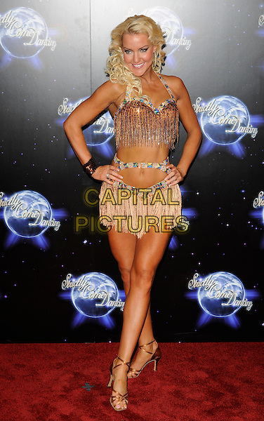 NATALIE LOWE .At the Strictly Come Dancing Launch Show TV recording, London, England, UK, September 8th 2010..full length beaded tassels dress costume hands on hips gold beige embellished diamante strappy sandals cut out midriff halterneck bra .CAP/CAN.©Can Nguyen/Capital Pictures.