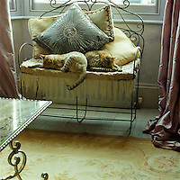 A pair of cats sleep through the afternoon on an antique wrought-iron bench piled with cushions