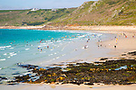 Coastal scenery with busy crowded sandy beach, Sennan Cove, Land's End,  Cornwall, England, UK
