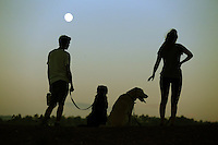 Owners and their dogs rest after a long walk at Yorba Regional Park in Yorba Linda as the full moon rises.