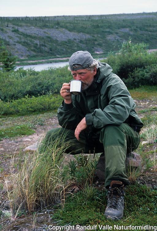 Mann drikker kaffe ved Thelon River, Canada. ---- Man drinking coffe beside Thelon River, Canada.
