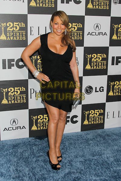 MARIAH CAREY .25th Annual Film Independent Spirit Awards - Arrivals held at the Nokia Event Deck at L.A. Live, Los Angeles, California, USA, 5th March 2010..indie full length black smiling hand on hip dress cleavage open toe shoes platform peep silver clutch bag bracelets .CAP/ADM/MJ.©Michael Jade/AdMedia/Capital Pictures.