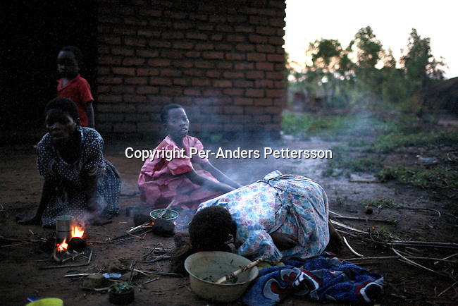 GALUFU, MALAWI NOVEMBER 12: Unidentified young girls light fires for cooking, after sunset on November 12, 2005 in Galufu, Malawi. The village has seen an increase in poverty the last few years due to drought and HIV/Aids. There's no electricity in the village. Southern Africa has been hit by a severe hunger crisis due to drought and poverty. An ever-increasing HIV/Aids rate adds to the misery. Malawi is one of the worst hit areas and Galufu village is a typical small village that has become victim of this poverty spiral. <br /> (Photo by Per-Anders Pettersson)