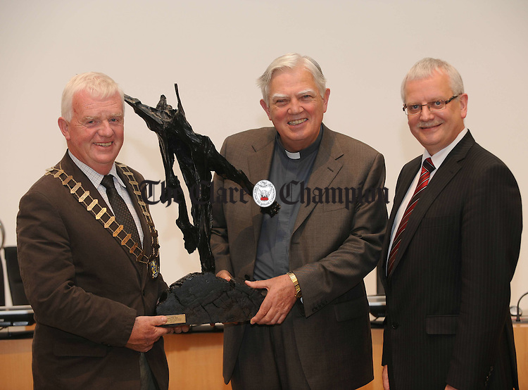 Bishop Willie Walsh is presented with a bog oak sculpture by Mayor of Clare Christy Curtin and County Manager Tom Coughlan at his civic reception in  Aras an Chlair. Photograph by John Kelly.