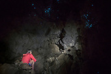 NEW ZEALAND, Northland, Woman Sitting below Glow Worms in Abbey Cave, Ben M Thomas