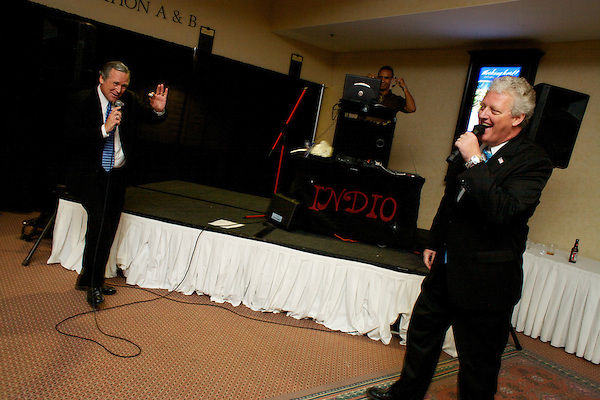 George W. Bush and Bill Clinton impersonators sing karaoke on stage at a celebrity impersonators convention in America