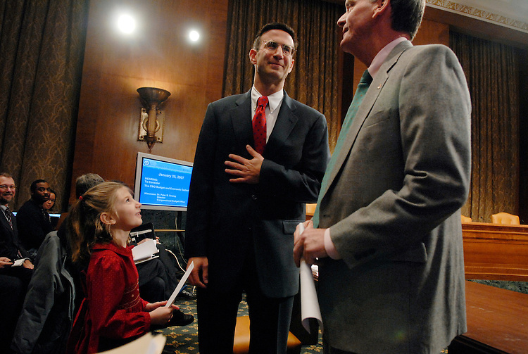 Leila Orszag, 6, her father Peter Orszag, center, director of the Congressional Budget Office (CBO), and ranking member Judd Gregg, R-N.H., talk before a hearing of the Senate Budget Committee, on the CBO's budget and economic outlook.