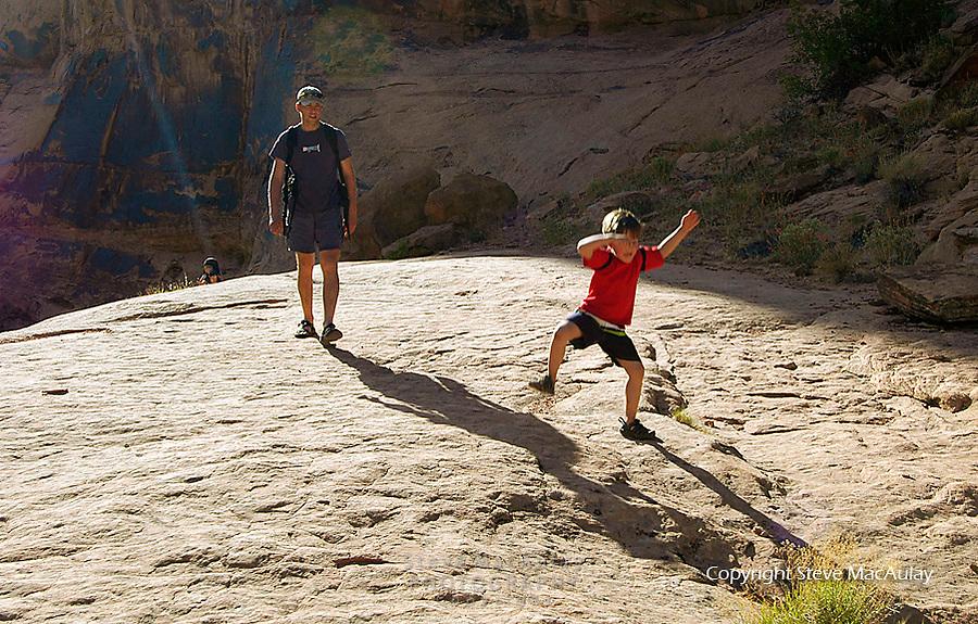 Family with kids enjoying a hike walk in the desert canyon along a creek, Utah