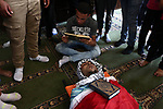 Relatives of Palestinian assailant Mohammad Marshoud ,30, after Israel released his body, mourn over his body at a mosque during his funeral at Balata refugee camp near in the West Bank city of Nablus, on July 14, 2018. Photo by Shadi Jarar'ah