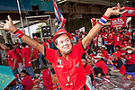 """Apr 4, 2010 - BANGKOK, THAILAND: A man with a Thaksin Shinawatra mask dances in front of the Red Shirts' main stage in Ratchaprasong intersection in Bangkok, Sunday, Apr. 4. Thousands of members of the United Front of Democracy Against Dictatorship (UDD), also known as the """"Red Shirts"""" and their supporters moved their anti government protests into central Bangkok Apr. 4 when they occupied Ratchaprasong intersection, the site of Bangkok's fanciest shopping malls and several 5 star hotels. The Red Shirts are demanding the resignation of current Thai Prime Minister Abhisit Vejjajiva and his government. The protest is a continuation of protests the Red Shirts have been holding across Thailand. They support former Prime Minister Thaksin Shinawatra, who was deposed in a coup in 2006 and went into exile rather than go to prison after being convicted on corruption charges. Thaksin is still enormously popular in rural Thailand. This move, away from their traditional protest site in the old part of Bangkok, has gridlocked the center of the city and closed hundreds of stores and restaurants and several religious shrines. There has not been any violence, but the government had demanded that the Red Shirts return to the old part of the city.   PHOTO BY JACK KURTZ"""