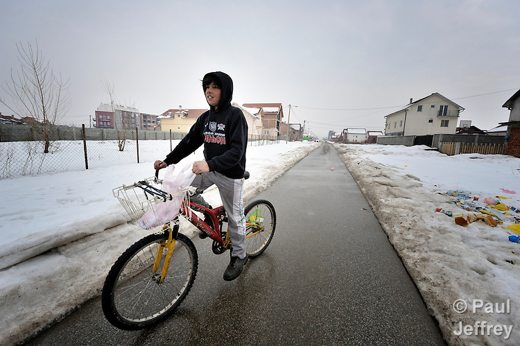 A Roma boy bicycles through the Zemun Polje Roma neighborhood of Belgrade, Serbia.  Many of the children hre are from refugee families that fled from Kosovo.