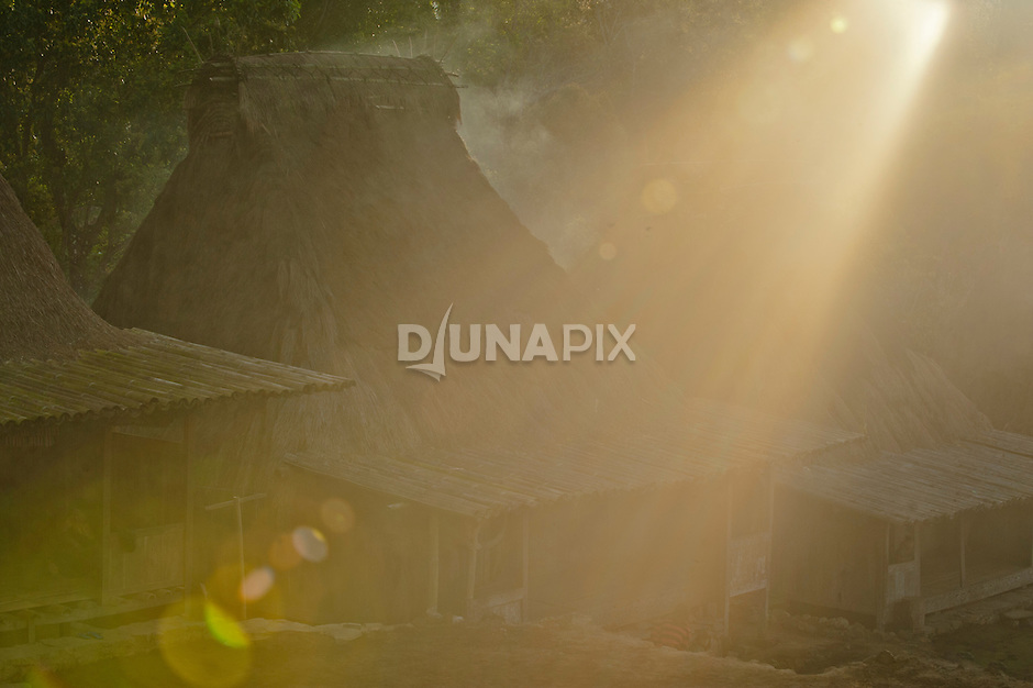 Morning sun's rays around traditional homes, Luba Village, near Bajawa, Flores, Indonesia