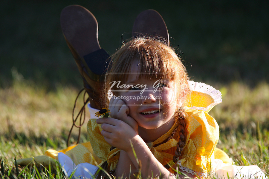A young smiiling girl holding a flower