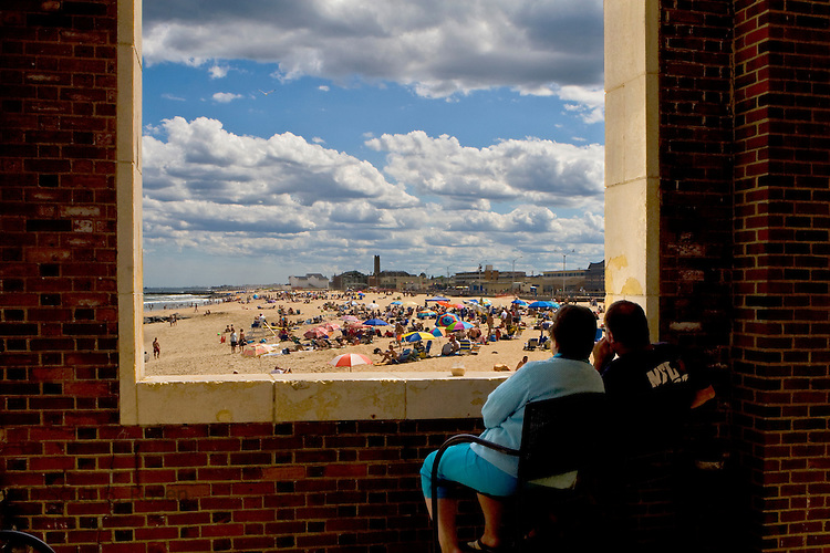 Couple looking through large opening of Convention Hall onto beach and ocean, Asbury Park, New Jersey