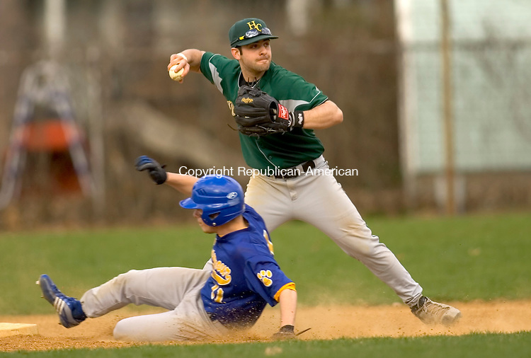 SEYMOUR, CT-09 APRIL 2009-040909JS02--Holy Cross' Kyle Tehan makes a throw to first as Seymour's Jay Burns slides safely into second during their game Thursday at French Memorial Park in Seymour. <br /> Jim Shannon Republican-American