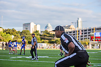 An official stretches prior to a high school football game between Anderson High School (Austin) and Westwood High School (Round Rock) at House Park in Austin, Texas on Thursday, September 3, 2015.