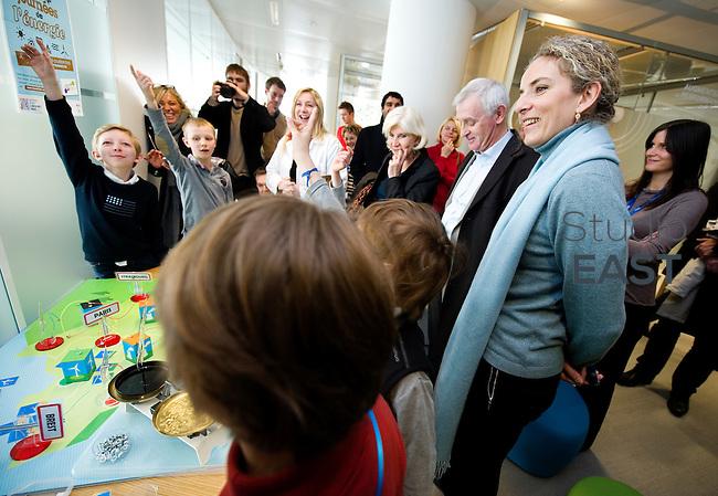 Mme Delphine Batho (droite, écharpe bleue), ministre de l'environnement et de l'énergie, regarde un jeu destiné à apprendre aux enfants les règles de l'équilibre énergétique, dans le showroom Recherche et développement de RTE, à Puteaux, près de Paris, France, le 30 mars 2013. Photo : Lucas Schifres