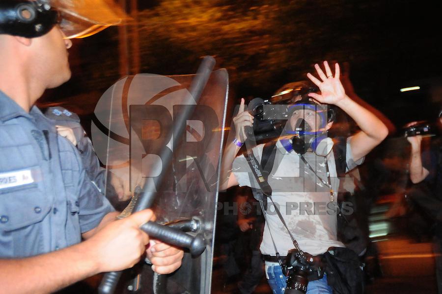 RIO DE JANEIRO, 22.07.2013 - Policial ameaça fotografo na Rua Pinheiro Machado durante confronto entre ativistas e policiais militares ao final de um protesto realizado nesta segunda-feira, 22, próximo ao Palácio Guanabara, sede do governo do Estado do Rio, em Laranjeiras, na zona sul do Rio. A manifestação foi mantida a cerca de 200 metros do palácio e era pacífica até as 19h45, quando ativistas lançaram um coquetel molotov na direção dos policiais. Um policial foi atingido e sofreu queimaduras superficiais. Os PMs revidaram com bombas de efeito moral. O papa Francisco já havia deixado o local. Sete pessoas foram detidas e pelo menos três ficaram feridas. (FOTO: SANDRO VOX / BRAZIL PHOTO PRESS).