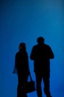 Silhouettes of people against a blue background