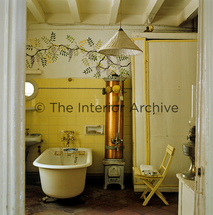 A copper stove used to boil the water stands next to the roll-top bath in this rustic bathroom decorated with hand-painted wisteria