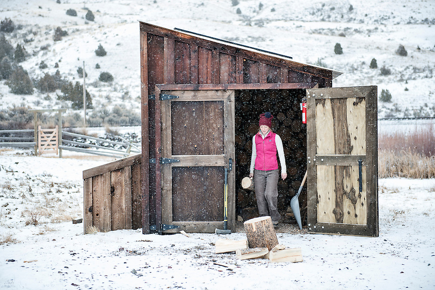 A woman chops wood during a snowstorm at the Henneberry-Ney Homestead on the Beaverhead River near Dillon, Montana.