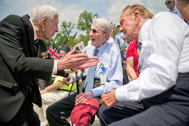 UNITED STATES - MAY 8: Former Sens. John Warner, R-Va., center, and Bob Dole, R-Kan., right, talk with Jon Naar, 95, who served with the the British Special Operations Executive, during a ceremony at World War II Memorial on the Mall to commemorate the 70th anniversary of the victory in Europe, known as VE Day, May 8, 2015, which featured flyovers by World War II era aircraft. Warner served in the Navy and Marines and Dole was wounded in WWII while serving in the Army.(Photo By Tom Williams/CQ Roll Call)