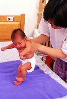Mother holds newborn infant as it demonstrates the stepping reflex.