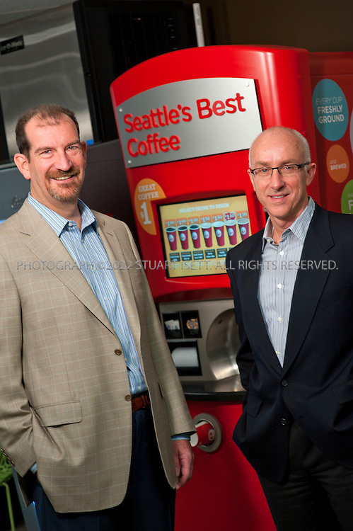 "2/10/2012--Bellevue,WA, US..Coinstar CEO Paul Davis (right) and CFO J. Scott Di Valerio (left) at the company's headquarters in Bellevue, WASH. posing in front of on the company's new automated coffee kiosks...Coinstar has quietly shaken up retailing with kiosks that let people convert jars of loose change into wads of paper cash while its Redbox machines dispense DVD rentals for $1.29 a night. Now it's seeking to take its concept of ""automated retailing"" even further, with coffee machines that whip up gourmet lattes and peddle refurbished iPads and other electronics devices. It's unclear yet whether the new categories will be as big a hit as Redbox, which helped accelerate the decline of Blockbuster and turned Coinstar into the biggest renter of DVDs in the country. Although DVD rentals are still growing for the company, that business is threatened long term by the rise of streaming services like Netflix, prompting Coinstar to announce a deal on Monday with Verizon to jointly develop a DVD rental and streaming movie service...©2012 Stuart Isett. All rights reserved."