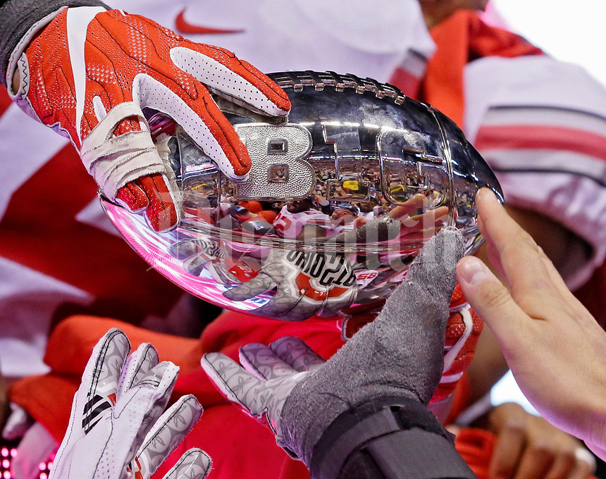 The Ohio State Buckeyes pass around the Amos Alonzo Stagg Championship Trophy while celebrating a 27-21 win over the Wisconsin Badgers in the Big Ten Championship game at Lucas Oil Stadium in Indianapolis on Sunday, December 3, 2017. [Barbara J. Perenic/Dispatch]