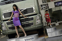 A model poses besides Volvo trucks at the Auto China 2004 exhibition in Beijing, China..