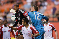 Kyle Porter (19) of D.C. United has the ball punched away from him by Joseph Bendik (12) of Toronto FC during a game at RFK Stadium in Washington, DC.  D.C. United tied Toronto FC, 1-1.