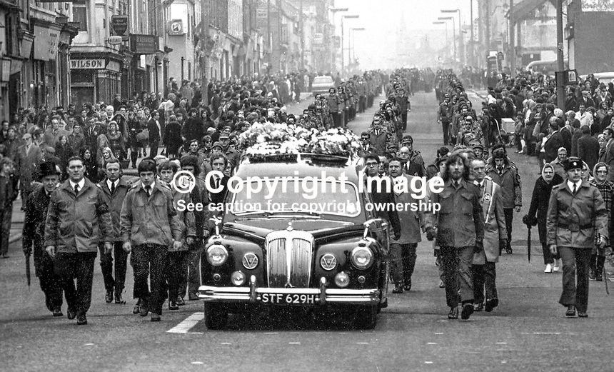 Funeral of the Good Samaritan - the funeral of 26 year old Protestant council worker, Samuel Llewellyn moves down the Shankill Road, Belfast, flanked by fellow council workers. Mr Llewellyn was shot in the Clonard area just off the Falls Road. He had just made his third journey in a van with hardboard sheets being used to board up the homes of Roman Catholics following a car bomb explosion. A 17 year old youth was held accountable and was given a &quot;natural life&quot; sentence, a legal precedent.  A natural life sentence is where the defendent would spend the rest of his life in prison. 197508190604a.<br />