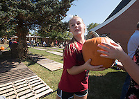 NWA Democrat-Gazette/J.T. WAMPLER Marleigh Hayes, 12, of Fayetteville works a pumpkin brigade Sunday Sept. 27, 2015 at Sequoyah United Methodist Church in Fayetteville. The congregation worked about two hours unloading several thousand pumpkins trucked in from Farmington New Mexico. The annual pumpkin sale benefits the church's youth ministries.