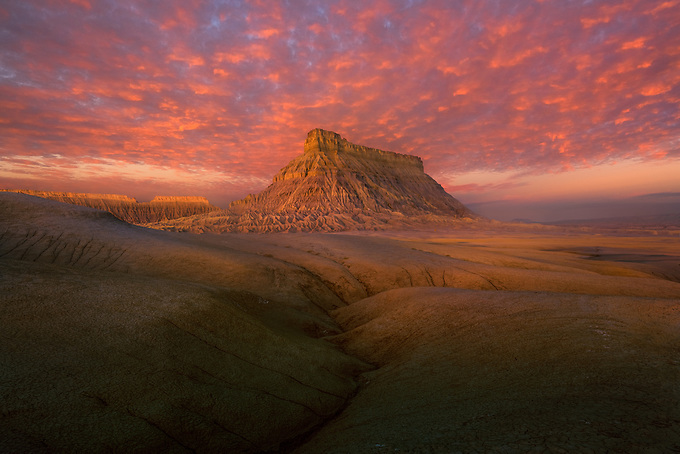 A flaming sunrise over Factory Butte, glowing in the morning light.