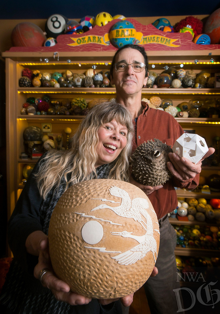 NWA Democrat-Gazette/BEN GOFF @NWABENGOFF<br /> Donna and Kelly Mulhollan, who are the folk music duo Still on the Hill, pose for a photo Saturday, Dec. 22, 2018, in  the living room of their Fayetteville home. They have named their living room The Ozark Ball Museum, where they display their collection of spheres of all kinds.