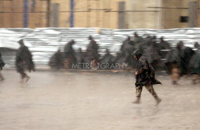 SULAIMANIYAH, IRAQ:  A member of the Kurdish security forces runs through the streets in the heavy rain...Tension continues to grow in the semi-autonomous region of Iraqi Kurdistan as protesters clash with police on a 5th day of unrest...Photo by Haedar Omar