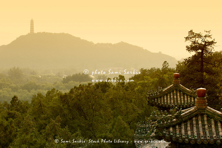 Pavilion rooftops and lush foliage as seen from the Summer Palace, Beijing, China.