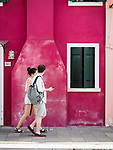 Tourists walking in the colorful village of Burano, Italy.